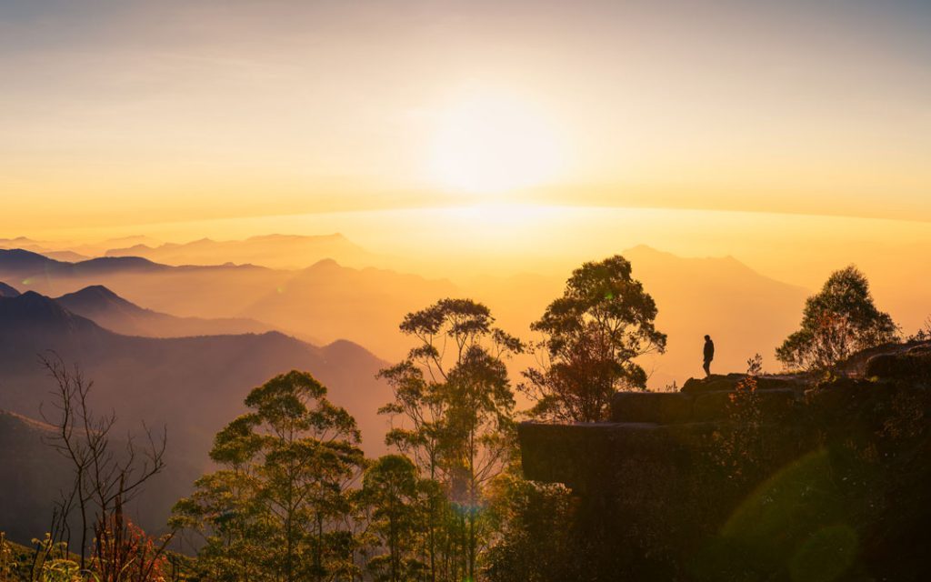 Silhouette of a woman watching the sunrise at Dolphin's nose in Kodaikanal, India