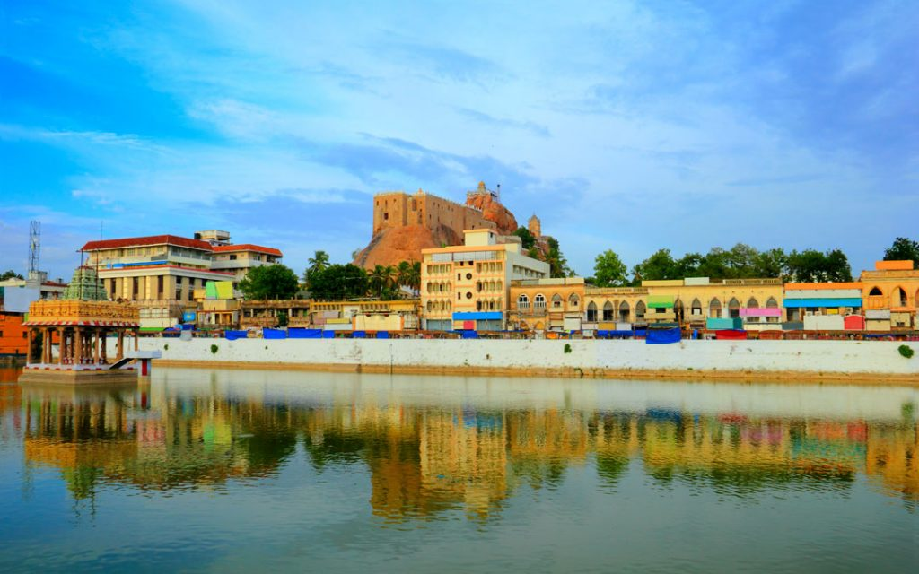Beautiful scenic view of Trichy (Tiruchirapalli) city with colorful houses, ancient Rock Fort (Rockfort) and Hindu temple reflected at calm pond water, Tamil Nadu.