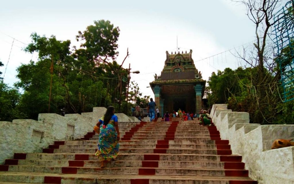 a lady climbing on the steps of the temple hill to visit the temple.